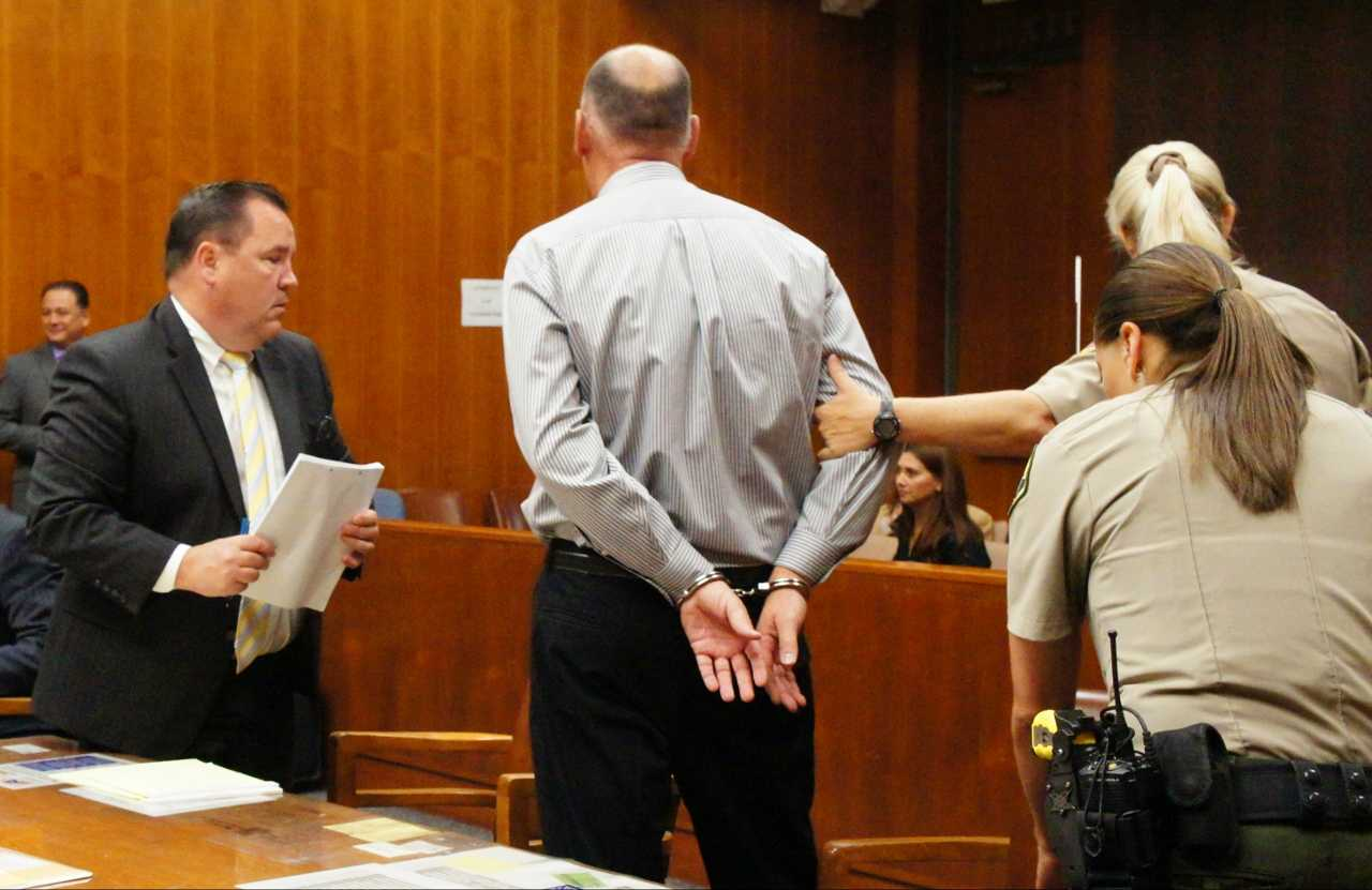 Deputies lead a handcuffed Holzworth from the courtroom May 29.