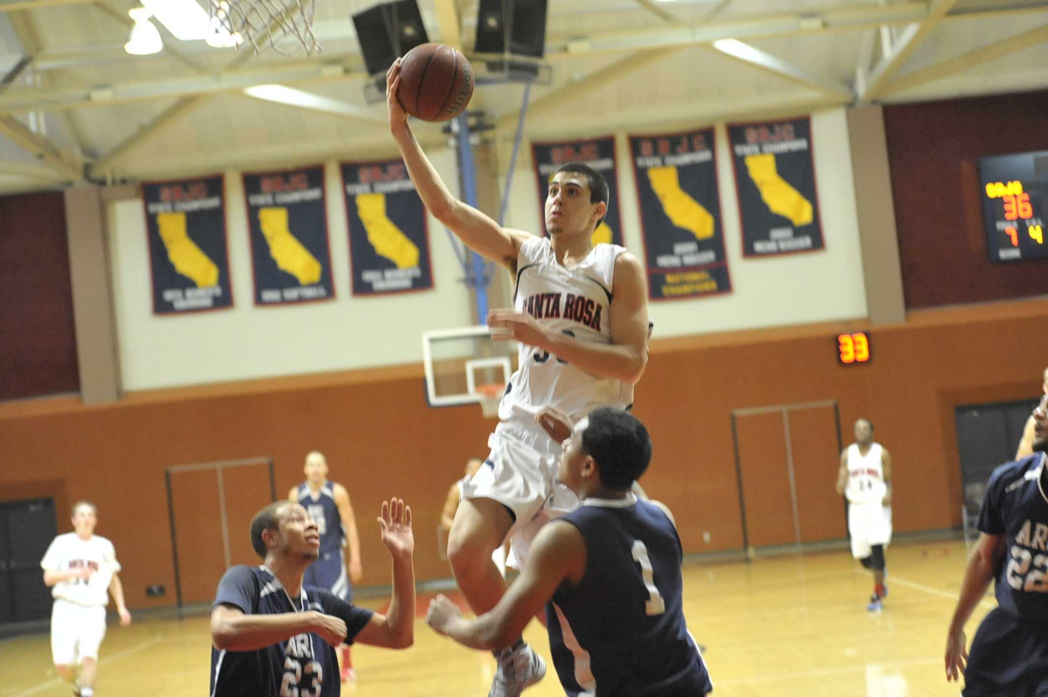 Men's basketball player Brian Johnson finishes a layup against American River College.