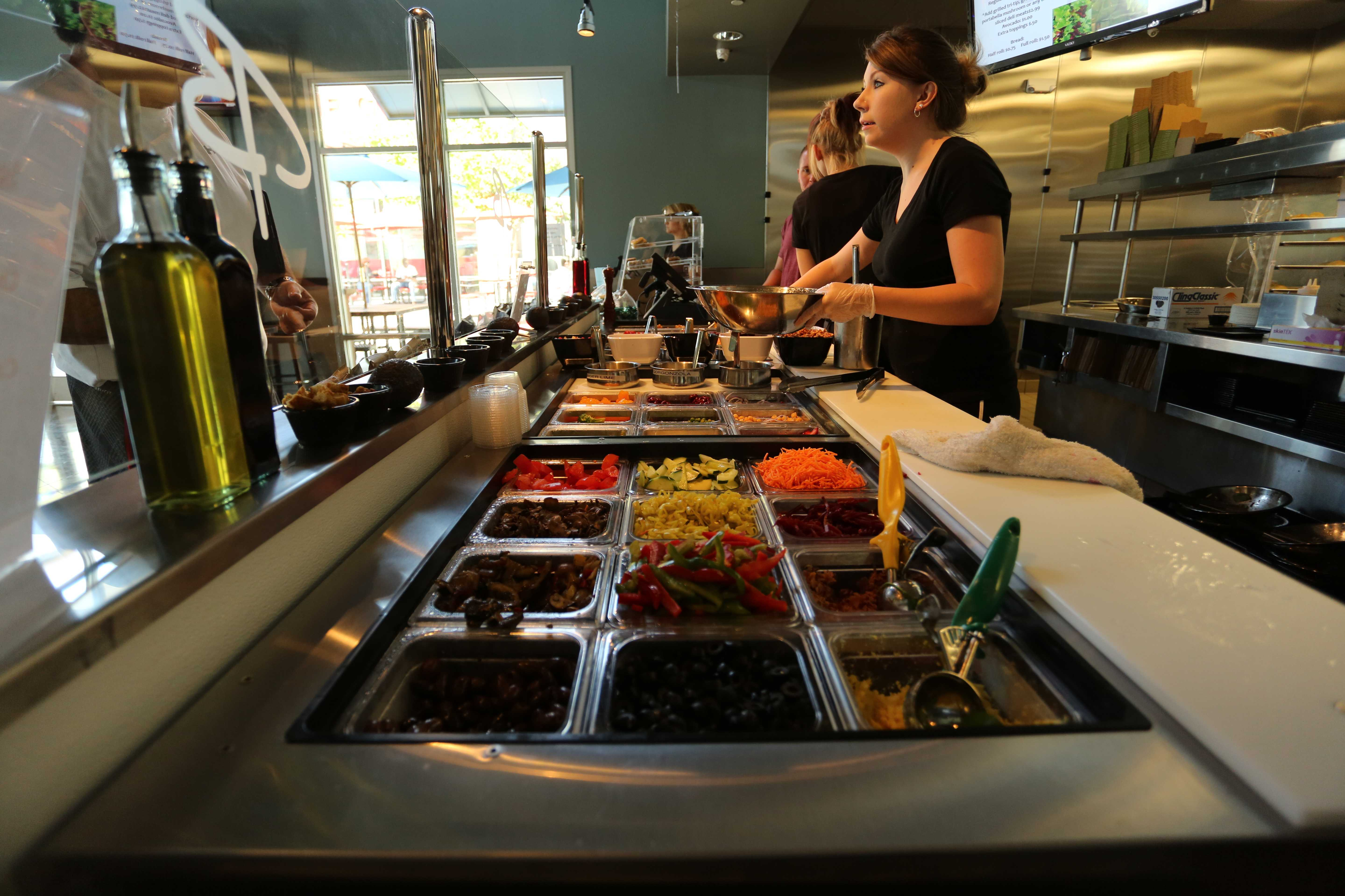 A server prepares a personalized salad for a customer at Bianchini's, a new restaurant on Mendocino Avenue that offers a variety of sandwiches and salads.