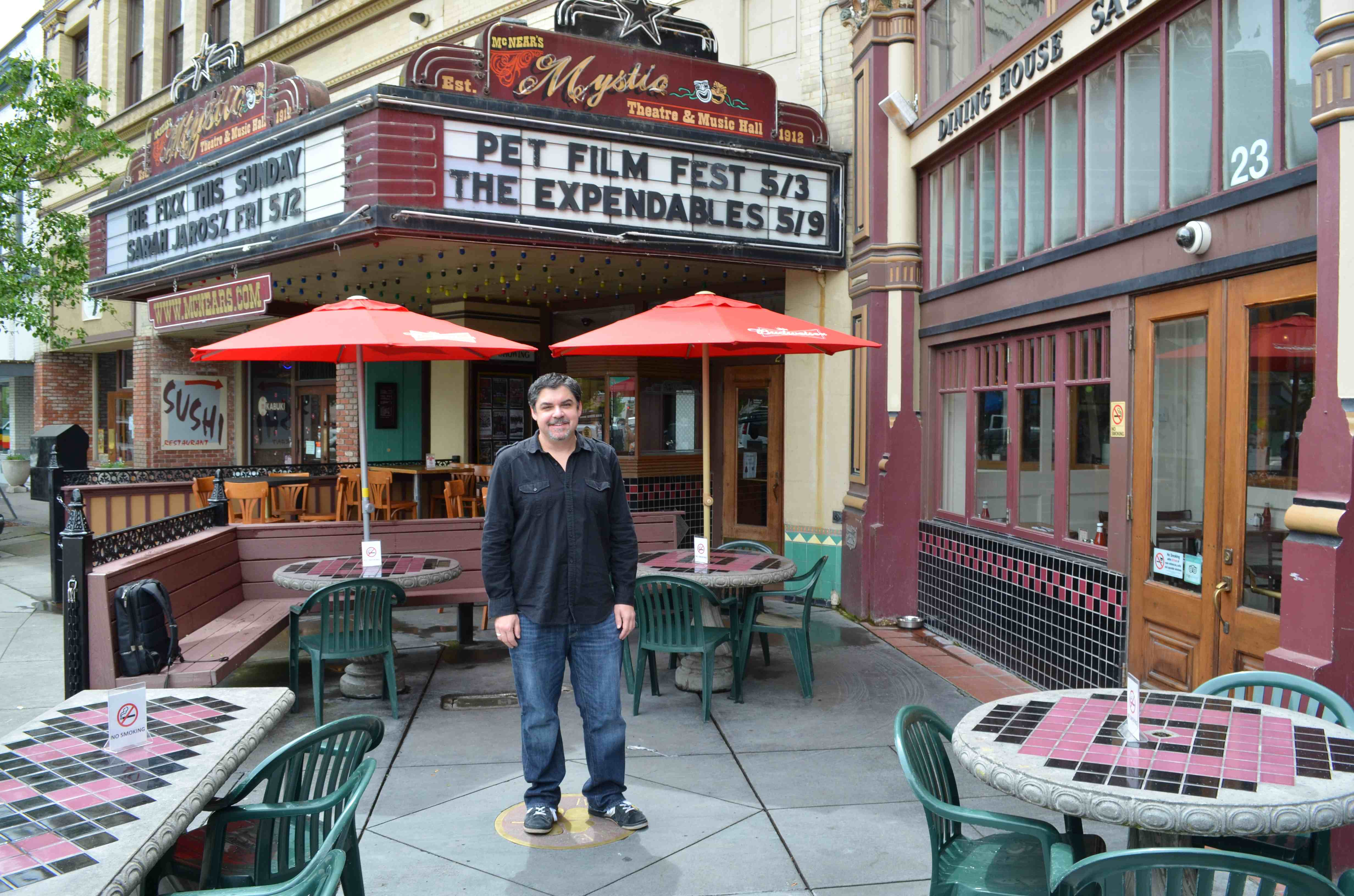 SRJC instructor MIke Traina poses in front of the Mystic Theatre in Petaluma.