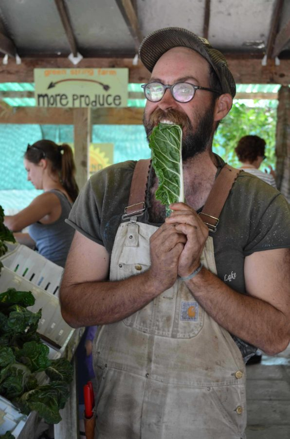 Former intern and current employee, Connor Maguire, 29 bites into a Green String Certified leaf of chard at the Green String Store in Petaluma, where the public are welcome to purchase the product of the interns' hard work.