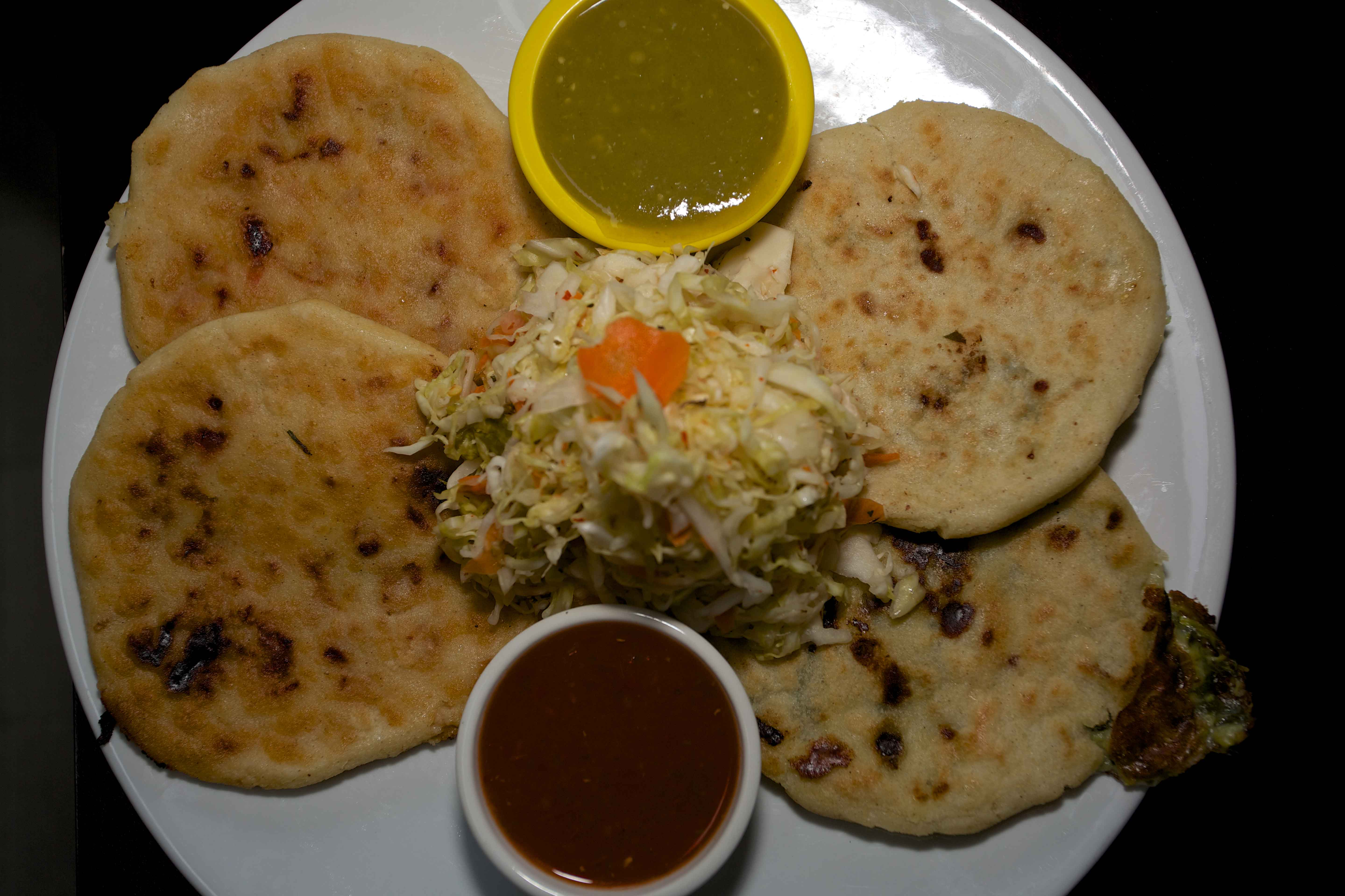 Pork, bean and cheese pupusas served with their curtido and salsa accompaniments from Pupuseria Salvadorena in Santa Rosa on Maple Avenue.