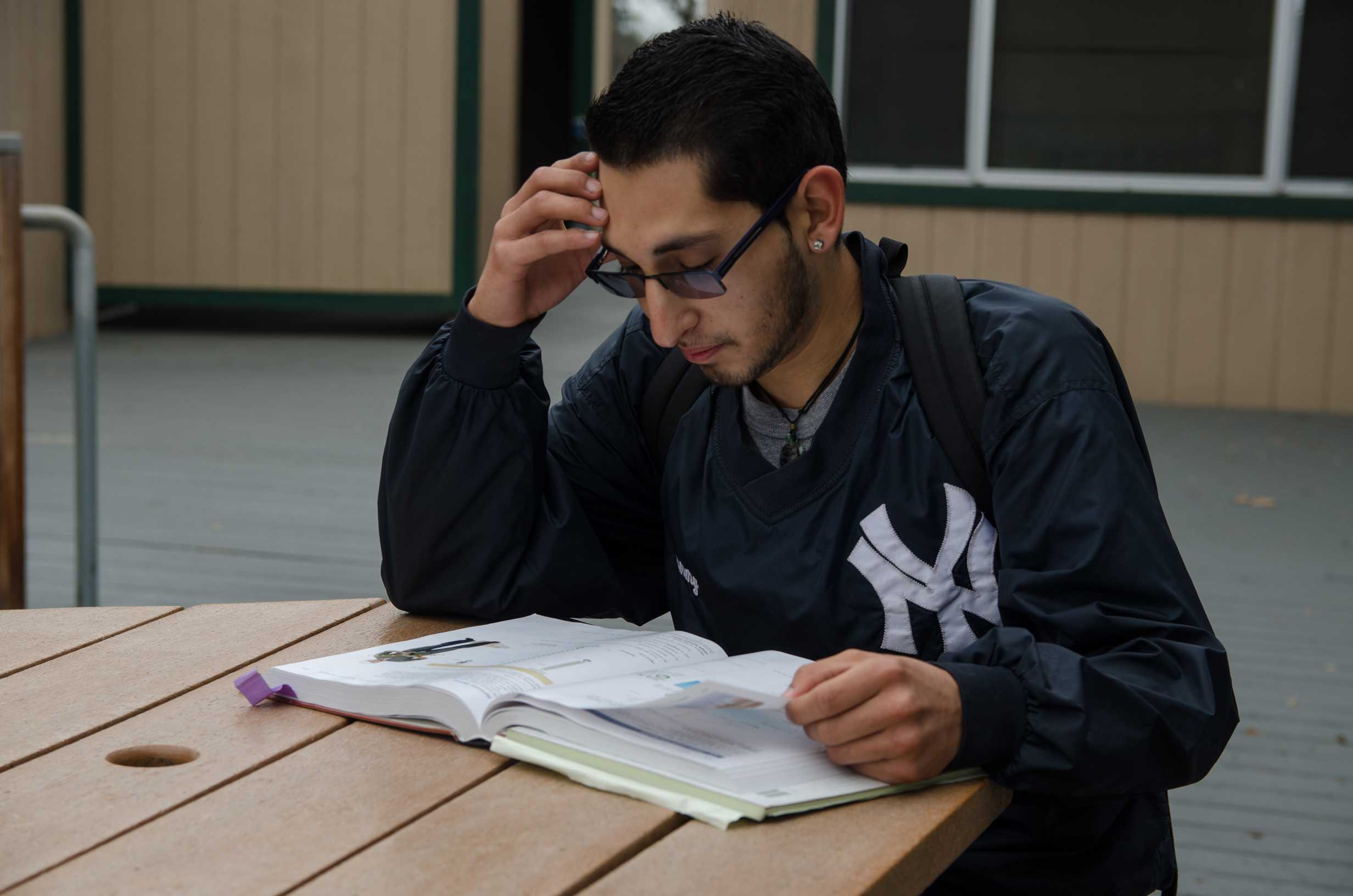 A student studies his textbook outside of class at SRJC at Analy Village.