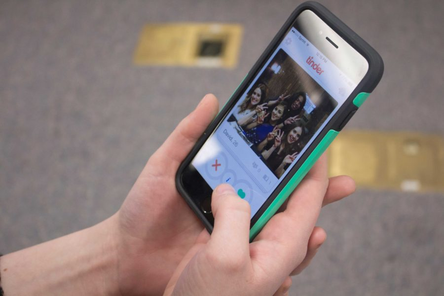 Kelsey Matzan swipes through Tinder, an app that lets you search through other nearby Tinder users, on her phone in search of a date.