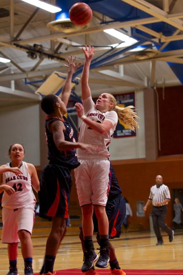 Jenna Dunbar sends the ball to the net over a Cosumnes River College defender Jan. 27 at Haehl Pavilion.