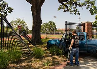 Santa Rosa Junior College student Brett W. looks upon the damange he caused to the fence of Bailey Field after fainting while driving.