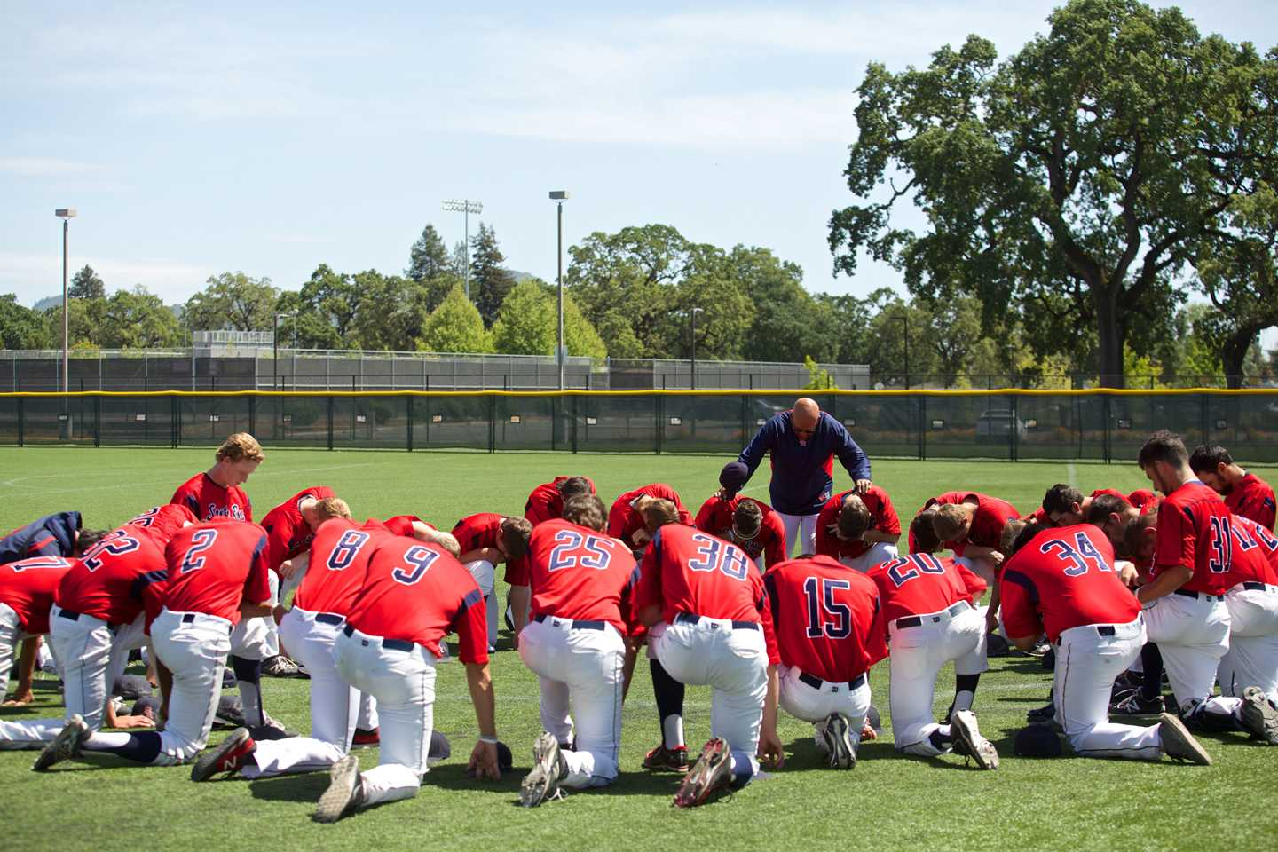 Tom Francois bows his head, along with SRJC Baseball in a moment of reflection before the final regular season game of 2015, against Sierra College April 24 at Sypher Field.