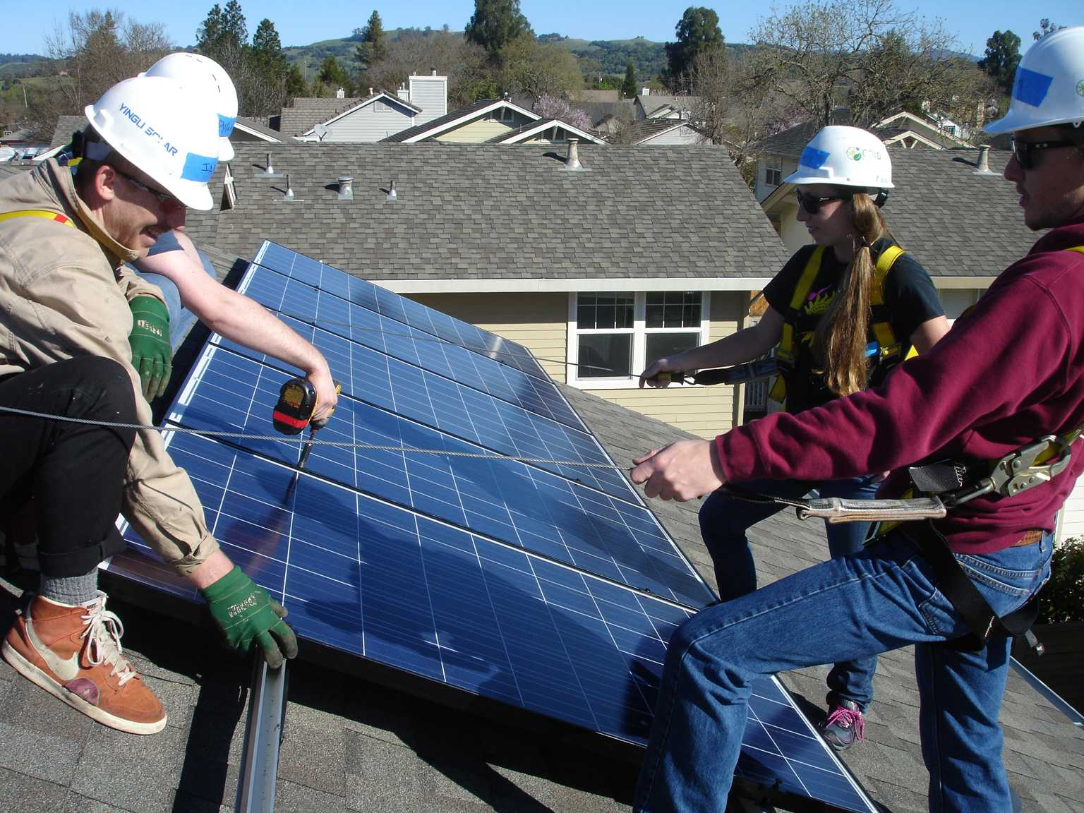 Students checking one of the solar panels on the roof of an SRJC building.