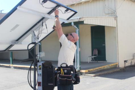 Professor Kevin Byrne prepares a solar panel for installation.