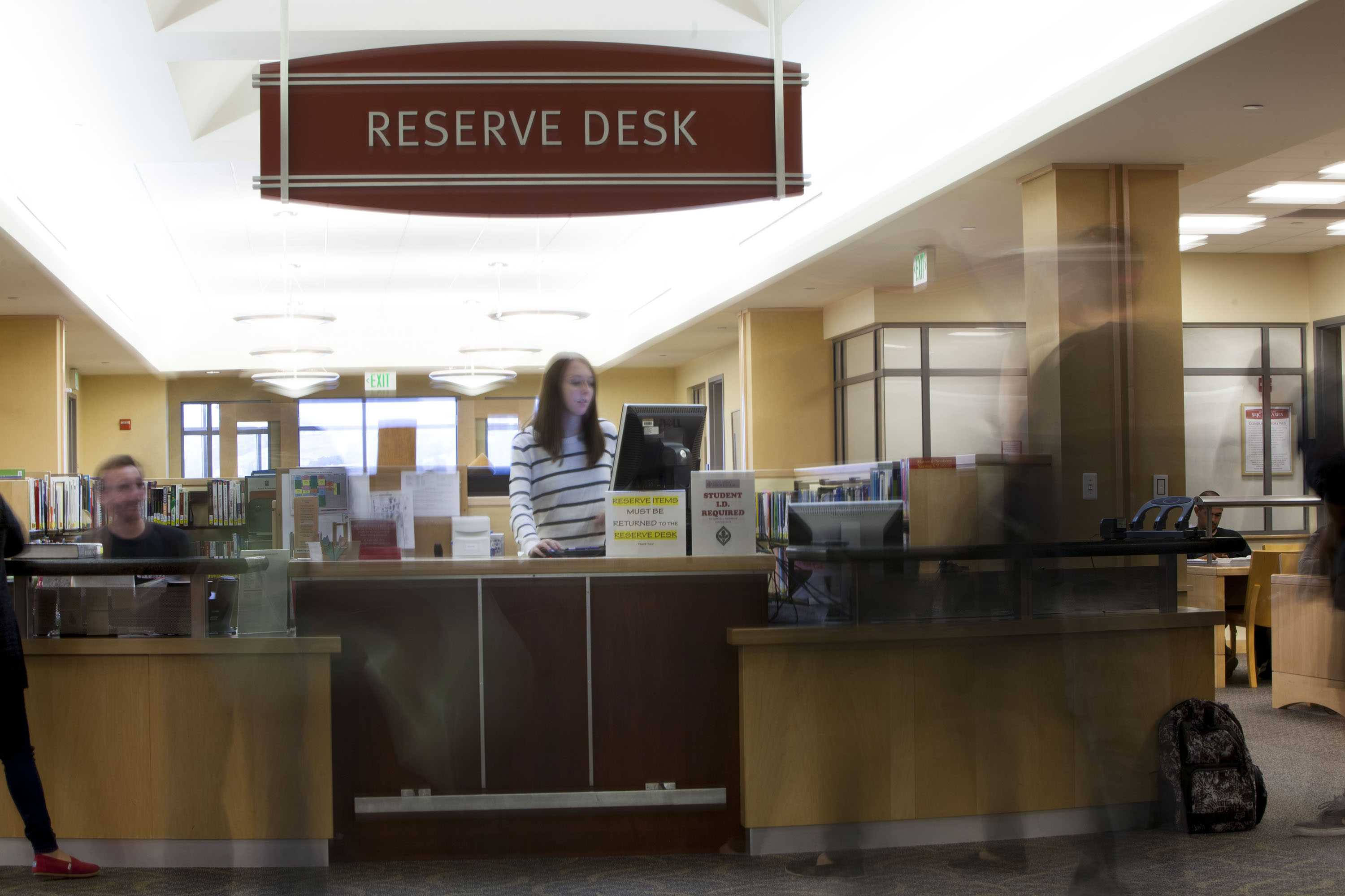 Student employees Hannah Sansom and Tyler Blatt assist check outs for short-term loans of textbooks at the reserve desk at the Doyle Library on the Santa Rosa Junior College campus Aug. 20.
