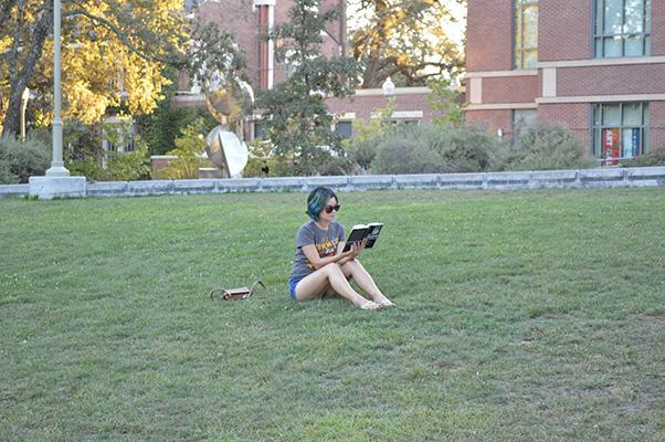 Kai+Schade+rests+on+the+lawn+in+front+of+Doyle+Library+enjoying+a+book+and+sporting+her+blue-green+hair.