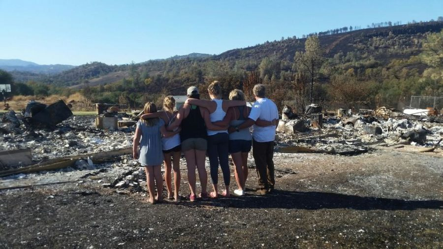 SRJC+student+and+basketball+player+Ashley+Hart+and+her+family+stand+in+front+of+the+remains+of+their+burned+house.