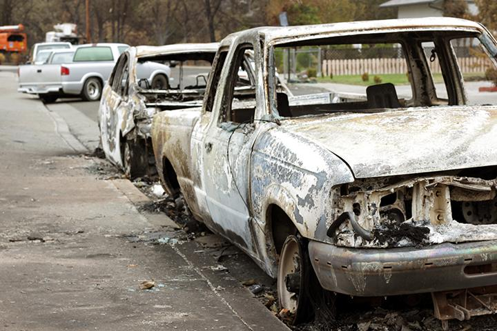 A line of vehicles remain parked after the fire spread from adjacent houses.