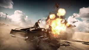 Mad Max and his mechanic lay waste to an enemy vehicle showering the wasteland with fire and scrap.
