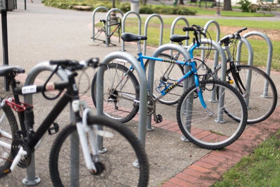 Student bikes stand idly in a bike rack outside of Plover Hall.