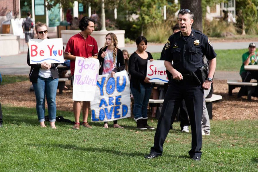 SRJC District Interim Police Chief Robert Brownlee addresses students on police's role in mass shootings with the SGA behind him with signs.