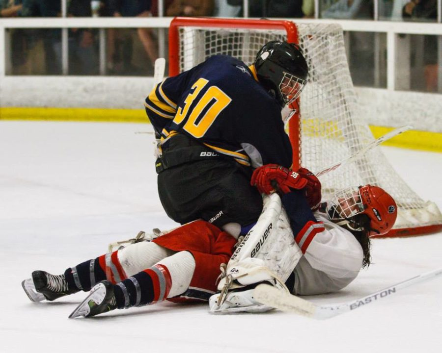 A UC Berkeley goaltender tackles former SRJC forward Chris Whitten after the Polar Bears' center attacked the net attempting to score. The two engaged in a heated scrum before officials pulled the skaters apart and penalized both teams.