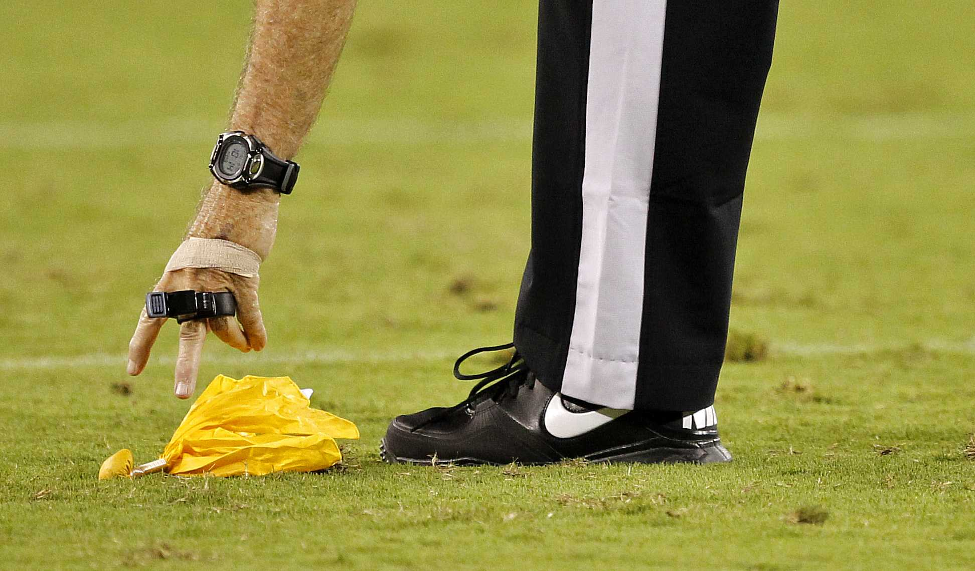 A referee picks up the yellow flag during the second half of an NFL preseason football game between the Denver Broncos and the Arizona Cardinals, Thursday, Aug. 30, 2012,in Glendale, Ariz. (AP Photo/Matt York)