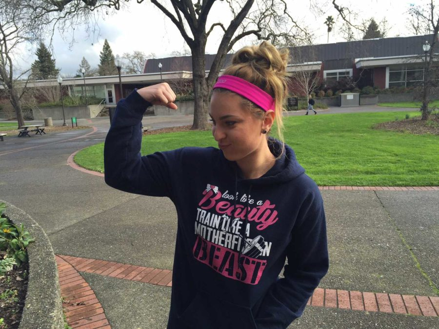 """I love feeling and being strong,"""" says Gigi Disidoro as she flexes on campus in between classes at SRJC."""