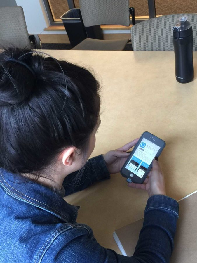 An SRJC student checks the Credit Karma app to view her credit score. Many students are struggling with accumulating debt.