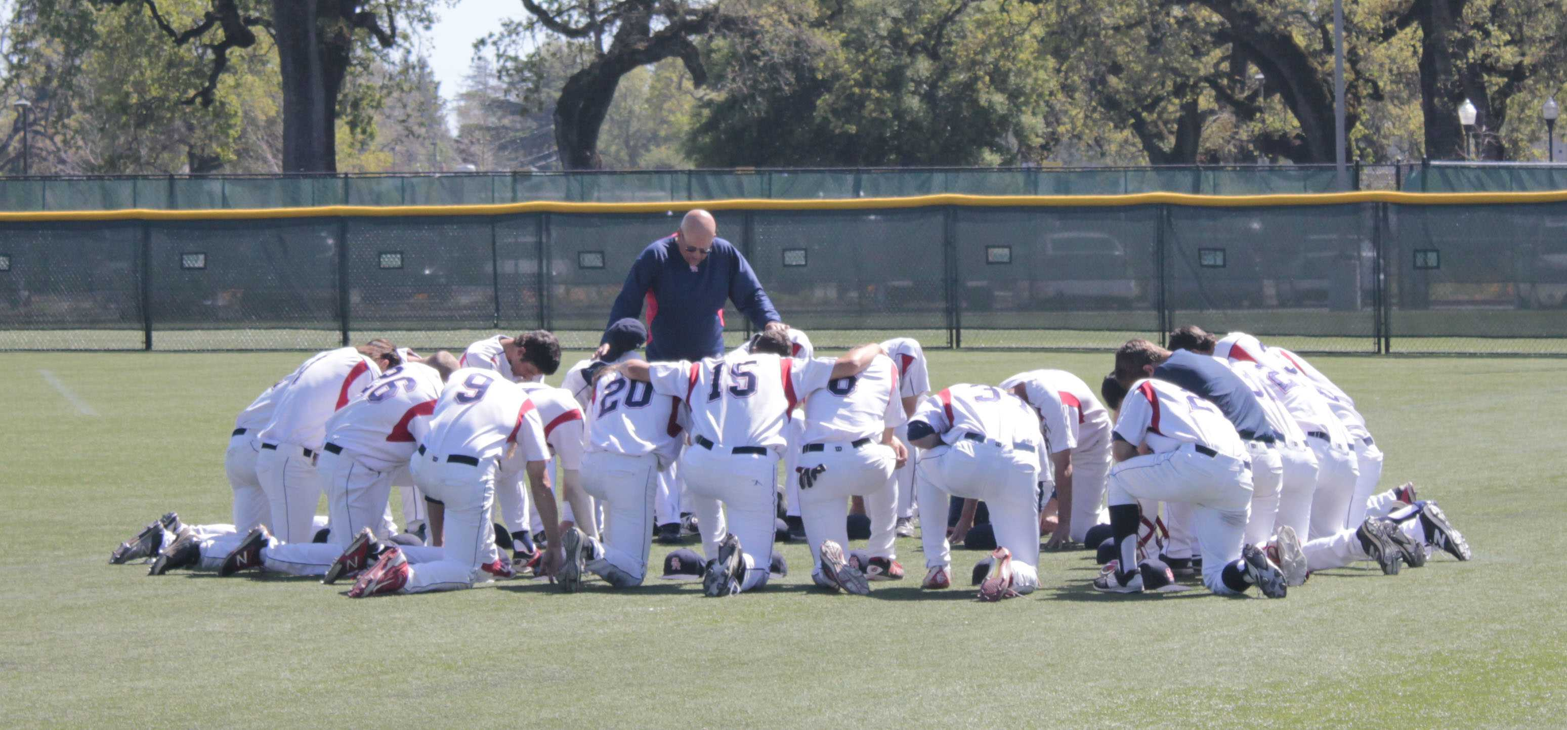 Assistant coach Tom Francois gathers the Bear Cubs together for a team prayer before the beginning of their game.