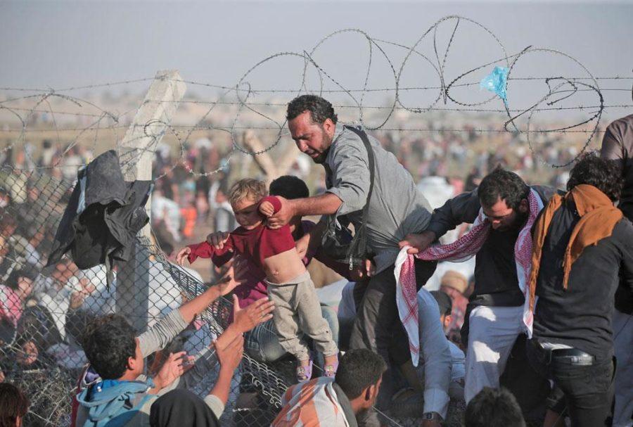 Refugees struggle to cross the border into Turkey.