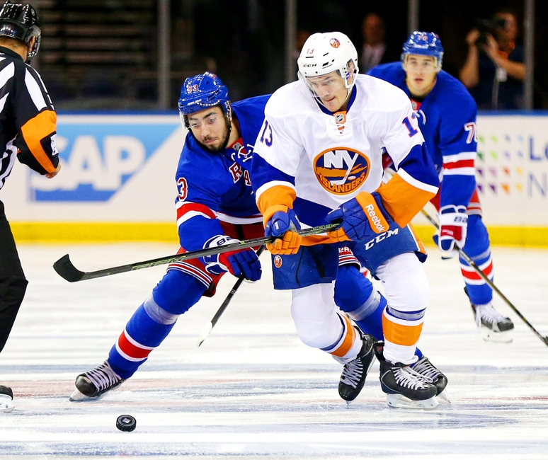 Sep 27, 2016; New York, NY, USA; New York Rangers center Mika Zibanejad (93) and New York Islanders center Mathew Barzal (13) battle for a loose puck during the first period during a preseason hockey game at Madison Square Garden. Mandatory Credit: Andy Marlin-USA TODAY Sports
