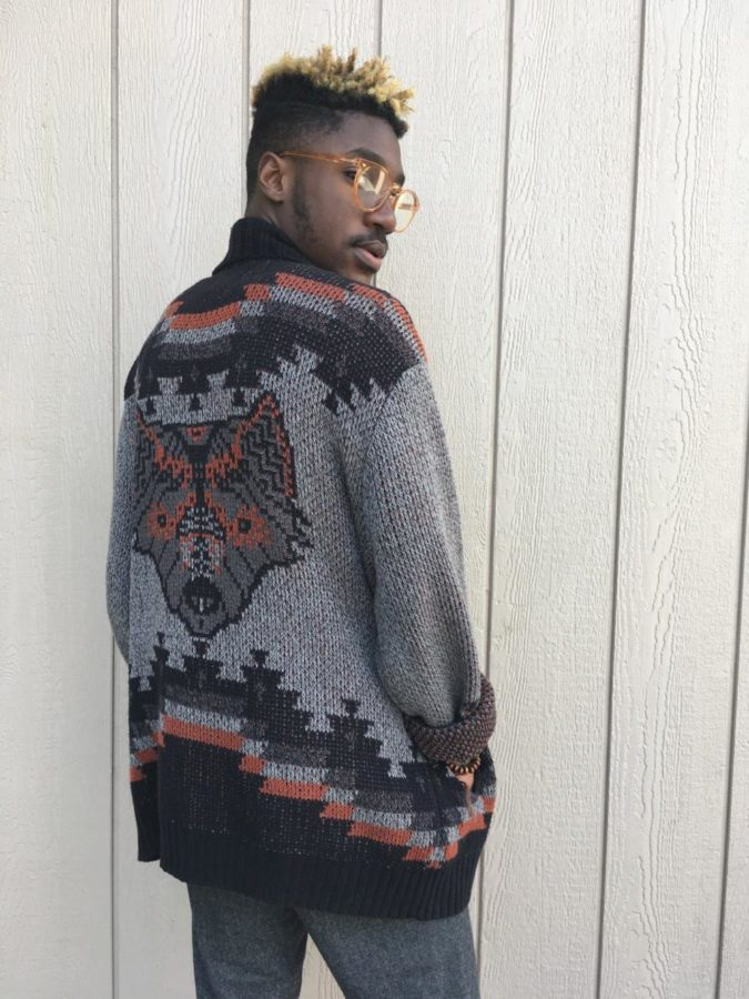 Diomande looking back at his fox-tribal knit sweater from Urban Outfitters.