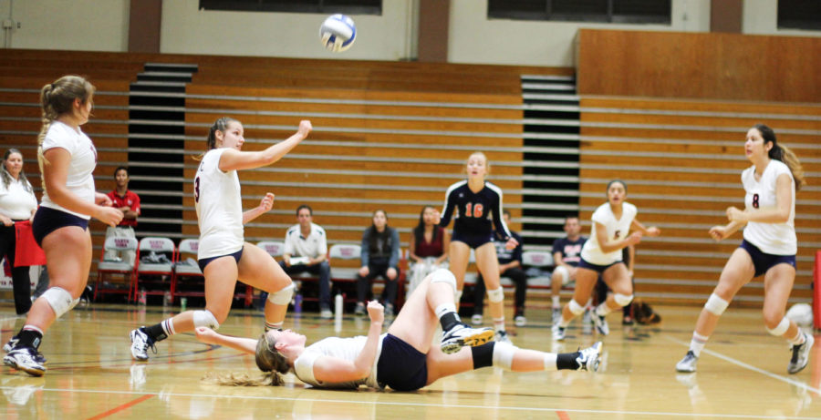SRJC womens volleyball team members furiously block a spike from their opponent.