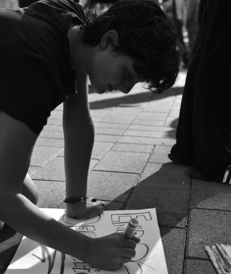 A protestor draws on poster board for a Sep. 2017 protest