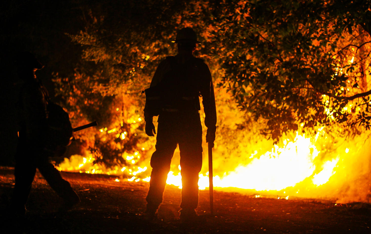 A firefighter watches a controlled burn outside the juvenile correctional facility near Kenwood.