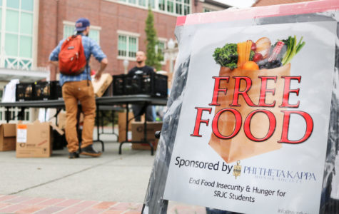 Vice President of Student Health Services Ryan Sansome helps a student at the Student Government Assembly and Phi Theta Kappa's Wednesday food bank outside Bertolini Hall. The student organizations are working to institutionalize a food pantry to combat food insecurity on campus. Photo by Charlotte Maxwell.