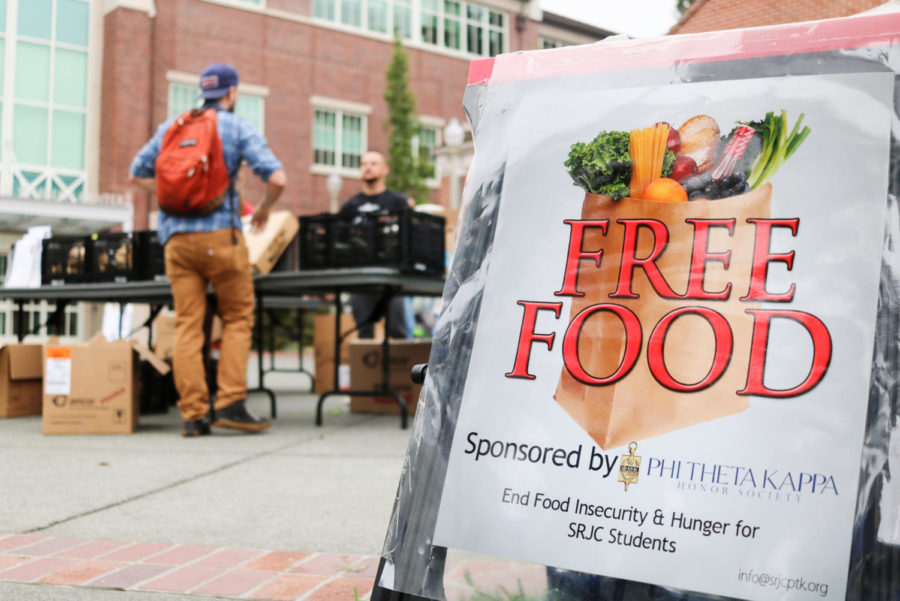 +Vice+President+of+Student+Health+Services+Ryan+Sansome+helps+a+student+at+the+Student+Government+Assembly+and+Phi+Theta+Kappa%E2%80%99s+Wednesday+food+bank+outside+Bertolini+Hall.+The+student+organizations+are+working+to+institutionalize+a+food+pantry+to+combat+food+insecurity+on+campus.+Photo+by+Charlotte+Maxwell.