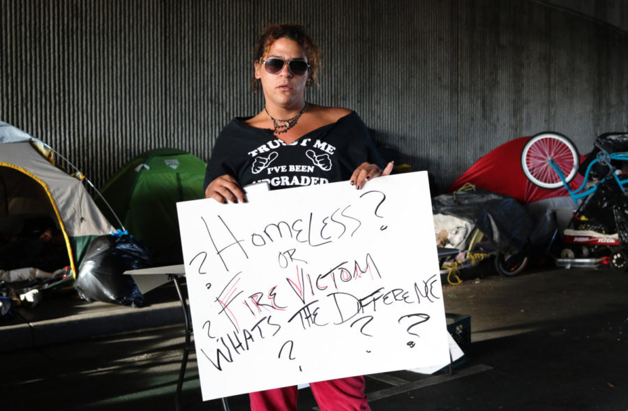 With garbage bins full of personal belongings, several activists helped the homeless recover their things. One woman displays her hand-made sign and protests the removal of their camp.
