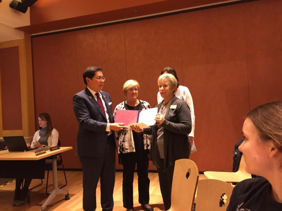 President Frank Chong presents an Honorary Associates Degree for Christina Hansen to her stepmother, Jennifer Watson.
