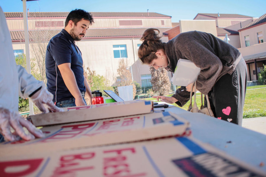 Student Ambassador Steven Blacencia hands out pizza to students in Rotary Plaza for Pizza Party day on Tuesday. Blacencia is a member of Anime club and helped coordinate events throughout the Petaluma campus' Welcome Week.
