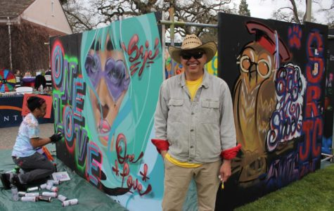 """Artist Martin Zuniga takes a break from screen printing to pose in front of his traveling art exhibit at SRJC's One Love Diversity Festival.  """"Since the market crash in 2008, it has been really tough for us artists. I started 'Quebo,' which means, 'What's up?' to take the art into the community. We bring it to schools or different events to make sure art gets to the people,"""" said Zuniga. Photos by Adeira Sherpa."""
