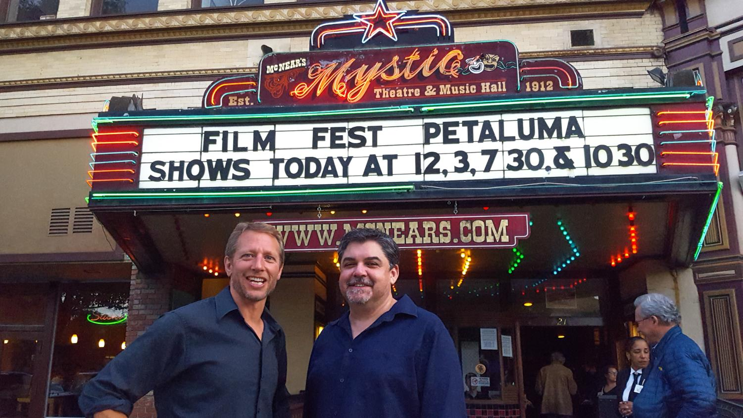 SRJC Media Instructor and Festival Director Mike Traina and fellow Instructor Brian Antonson pose in front of the historic Mystic Theater, the site of this year's Petaluma Film Festival.
