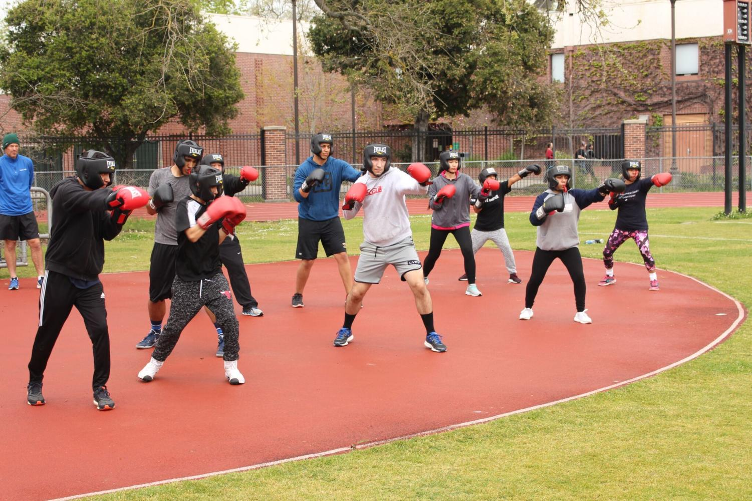 A Santa Rosa Junior College combat class practices boxing on Bailey Field.
