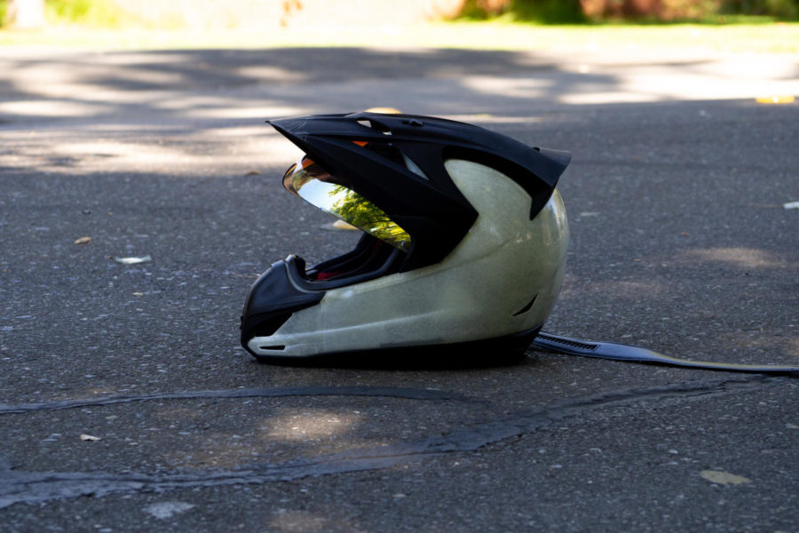 A motorcyclist's helmet lays on Elliott Avenue after a collision with a Honda minivan. The motorcyclist was rushed to the hospital with unknown injuries.