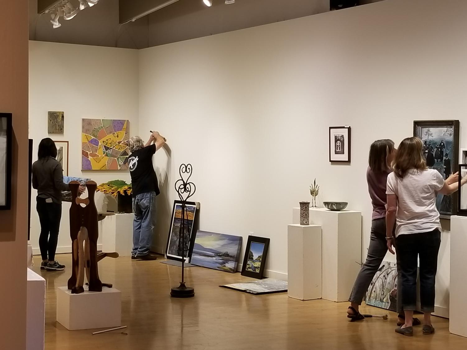 Artists install the Main Preview Exhibit for Art Trails Open Studios at Sebastopol Center for the Arts.
