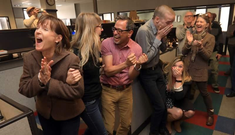 Espinoza (center) and colleagues celebrate the Press Democrat's Pulitzer win.