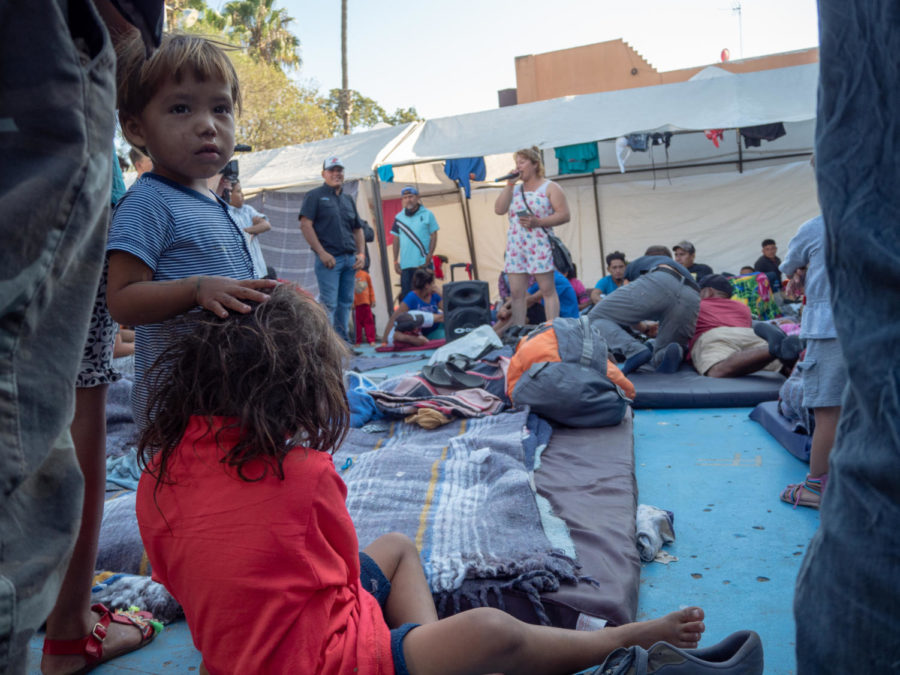 Two children among others in the caravan listen to a female entertainer.