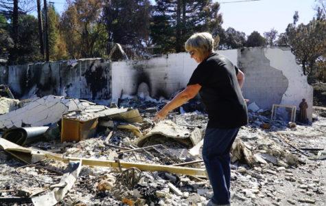 Tyra Benoit identifies bits of her belongings in the ash heap that was her home.