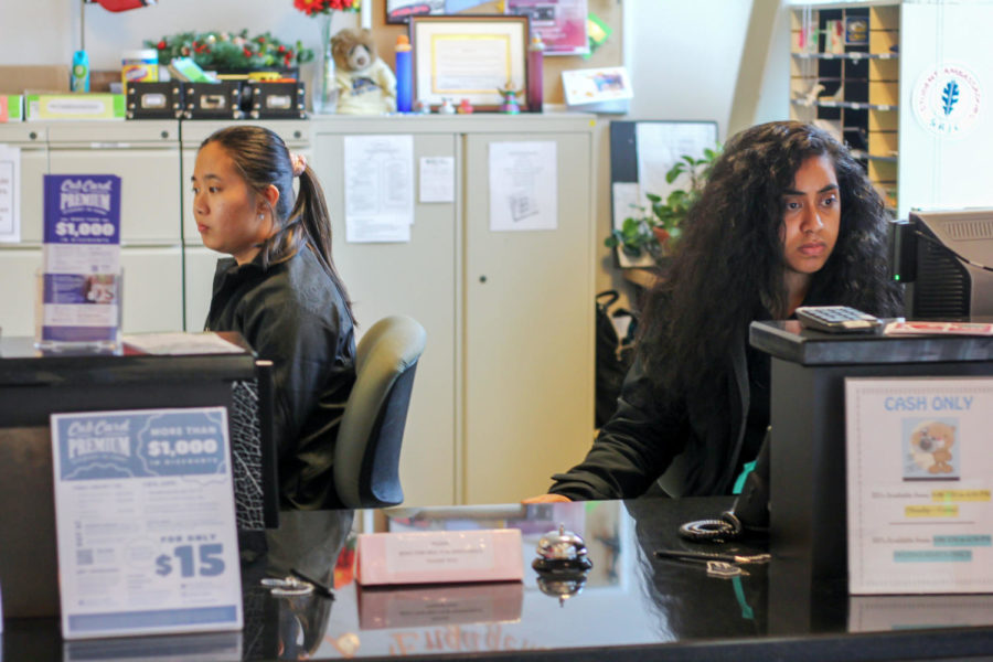 """At the Student Services desk, Student Ambassadors Jesse Pagulayan, 19 (left) and Anna Kidd, 21, (right) assist the students slowly filtering in throughout the day in between finishing their final assignments of the semester. """"It's usually very lively in here, but by the end of the semester no one wants to be on campus because of the stress,"""" Kidd said. """"I overhear conversations between students on campus and all they're talking about are grades, finals and tests, you can see the stress on their faces."""""""