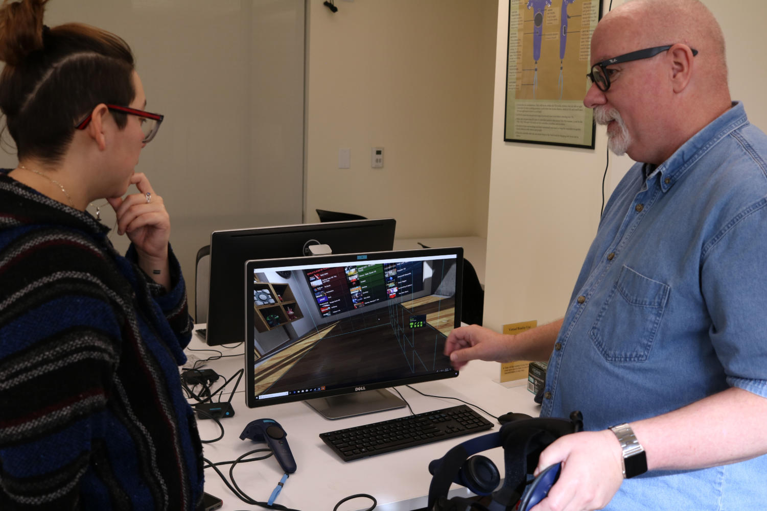 Instructor Robert Grandmaison teaches student Vanessa Mondragon how to use the Virtual Reality gear, available for student use in the new Digital Media Suites on the 2nd floor of Doyle Library.