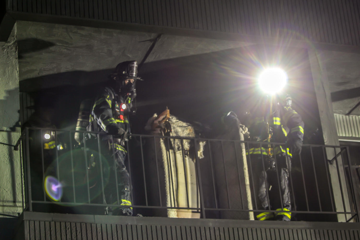 Two+firefighters+throw+the+remains+of+a+couch+off+a+second+story+balcony.