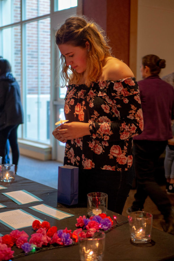 Sophie Ammerman, 20, SRJC psychology student holds a still-burning vigil candle as she reflects on the stories of sexual assault victims displayed on the vigil table.
