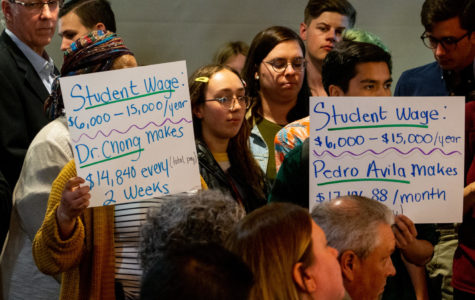 MEChA de SRJC members hold signs up toward the Board of Trustees to show their dissatisfaction in the board's current plan to increase student-employee wages before the April board meeting on Tuesday in the Student Activities Center.