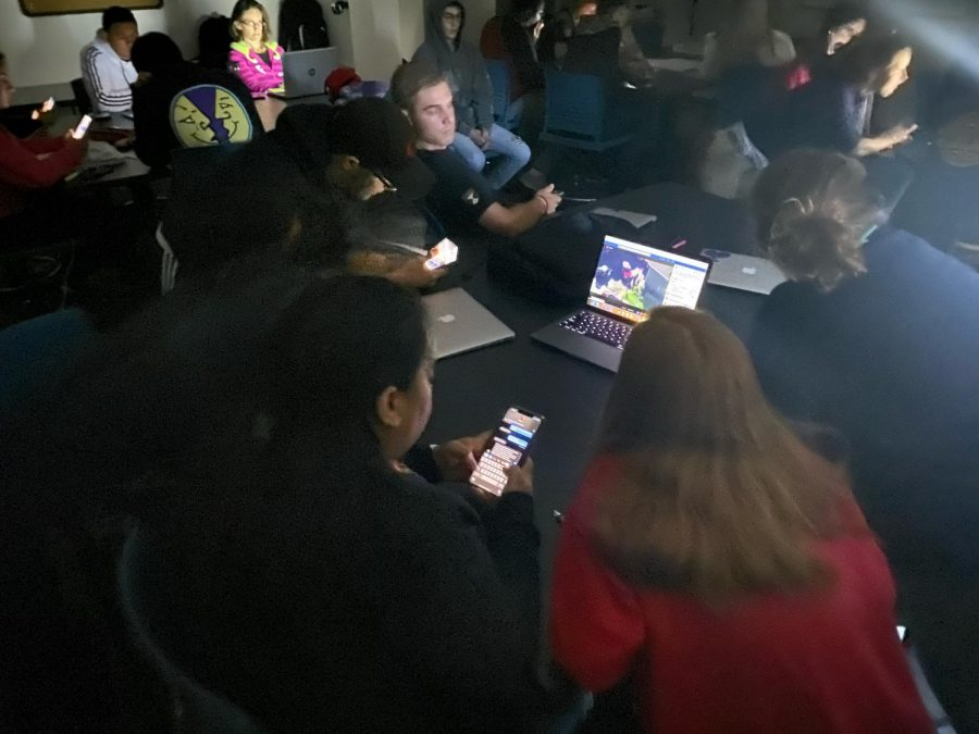 Students in anthropology lab watch an ABC7 news live stream in the dark during the Oct. 22 lockdown.